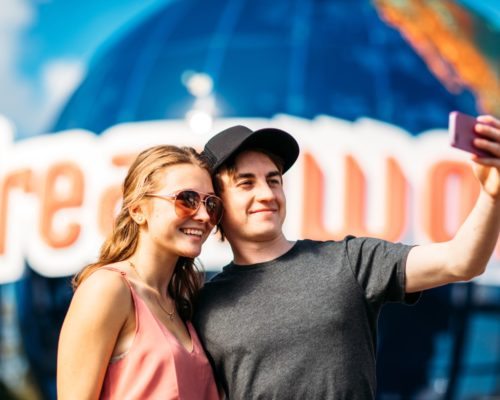 couple-taking-photo-on-phone-in-front-of-dreamworld-sign
