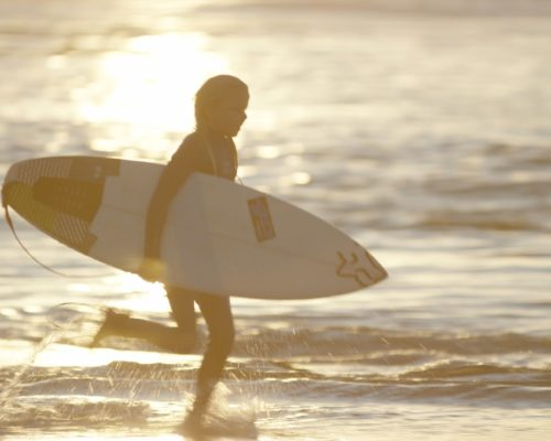 young-surfer-running-through-the-ocean-at-snapper